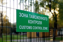 Green sign with the inscription in Russian and English: Customs control zone on the fence of metal rods
