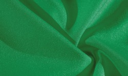 green silk. Smooth elegant green luxury silk fabric can be used as abstract background with copy space, close up. colorful texture