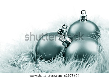 Green silver christmas baubles on feathers on a white background with space for text