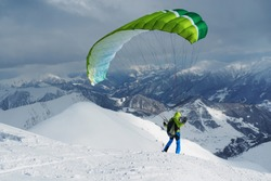 green skier starts with a paraglider in the highlands