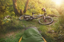 Green sleeping bag on a yellow inflatable mat with a mountain bike lying on a forest rock - awakening in the middle of beautiful nature, point of view photo. Staycations with bike.