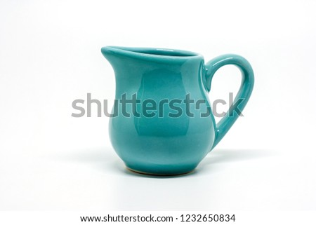 Green small ceramic pitcher on white background for utensil and dishware concept #1232650834