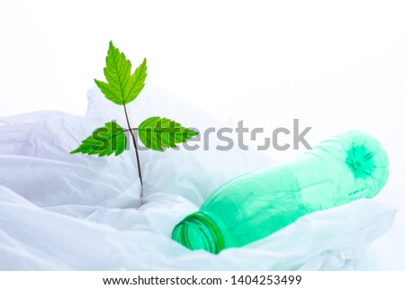 Green small sprig and plastic bottle on white polyethylene bag. Protection of nature and ecology from pollution of plastic products. Ecology care and ecological problems   #1404253499