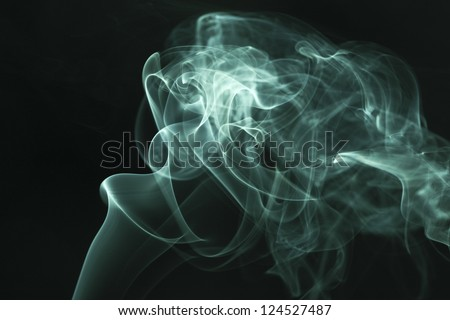 Green smoke rises up on a black background.