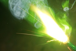Green smoke sparkler sparkling on dark background with some green color smoke on the deepavali / diwali celebration