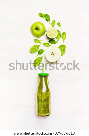 Green smoothie drink in bottle with straw  and  ingredients ( spinach,apple, lime )  on white wooden background, top view