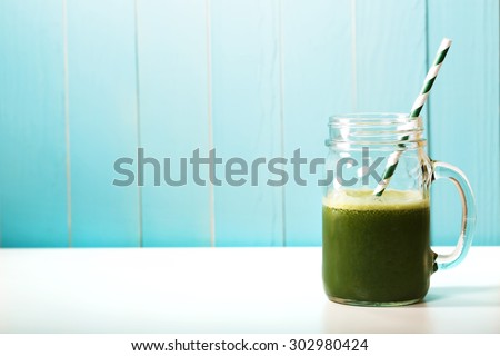 Green smoothie in masons jar with paper straw on blue wooden wall