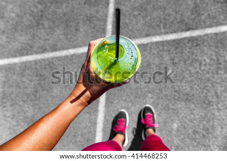 Green smoothie woman drinking plastic cup breakfast meal takeaway to go after morning run on city streets. Healthy lifestyle sporty person pov of hand holding glass with running shoes feet selfie. #414468253