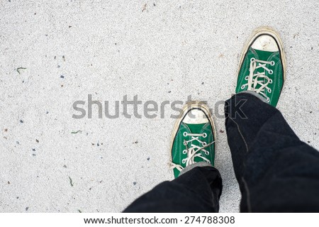 green Sneakers shoes walking on white Sand top view , Canvas shoes walking on white Sand