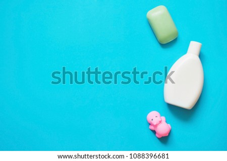 Green soap bar, white shampoo bottle and rubber toy hippo on a blue background. Flat lay beauty mockup. Top view photo bath products, toiletries #1088396681
