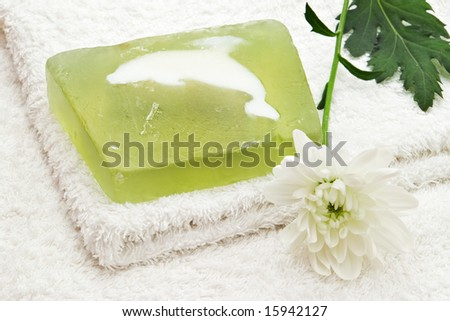 green soap on white towel and flower