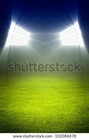 Green soccer field, bright spotlights, illuminated stadium