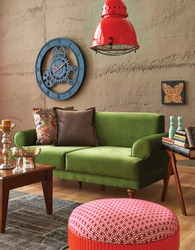 green sofa stone wall with modern red lamp