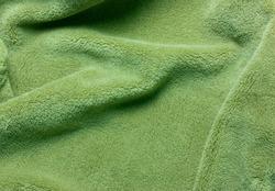 Green soft  fleece texture. The surface of a teddy crumpled microfiber rug