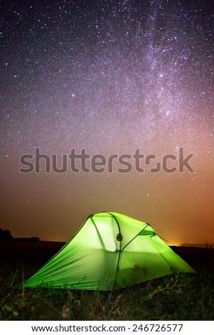 Green solo tourist tent under dark night sky full of stars and constella