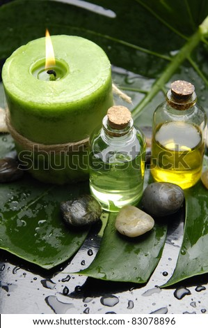 Green Spa-candle and massage oil with stones on leaf