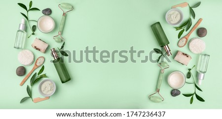 Green spa or wellness layout frame. leaves and body and face care tools and accessories on Green background, top view. Beauty  various eco friendly cosmetic and skin care products.space for text. ストックフォト ©