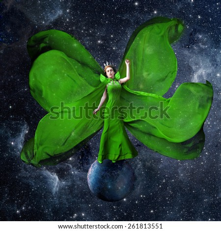 Green space queen. Beautiful woman in a fluttering dress standing and balancing on the planet in outer space. Fantastic art work. Elements of this image furnished by NASA