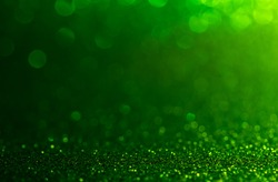 green Sparkling Lights Festive background with texture. Abstract Christmas twinkled bright bokeh defocused