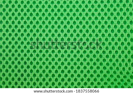 Photo of  green special textile mesh background. Polyester mesh with foam rubber for the manufacture of backpacks. Lining mesh with foam for the inside of a bag or clothes.