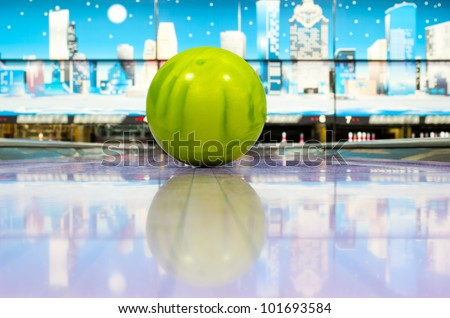 Green sphere ball standing on bowling lane before strike