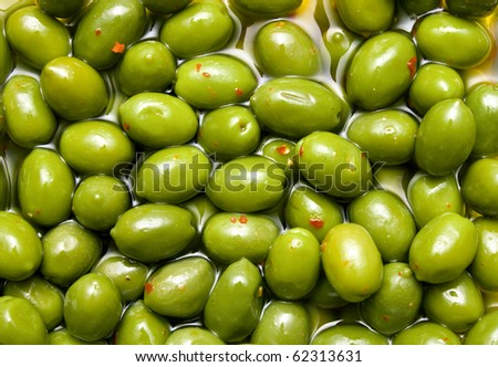Green spicy tasty olives background