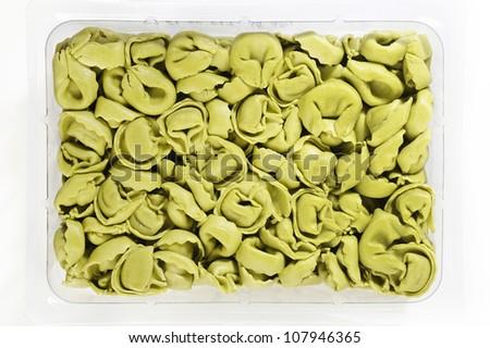 Green spinach tortellini in plastic box