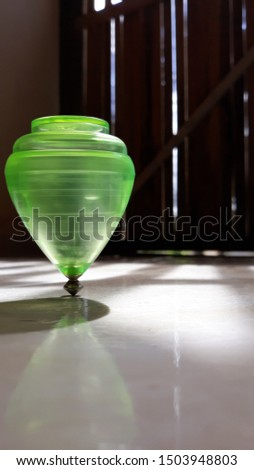 green spinning top spinning on the porch floor #1503948803