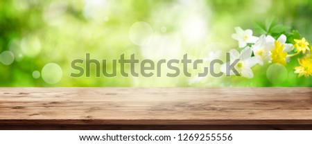 Green spring background with sunny bokeh and empty wooden table for a decoration