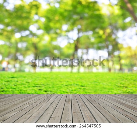 Green spring defocused abstract background and empty wooden platform
