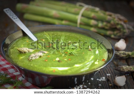 Green spring pureed asparagus soup in a bowl decorated with dill. Close up image, wooden background. Stock photo ©