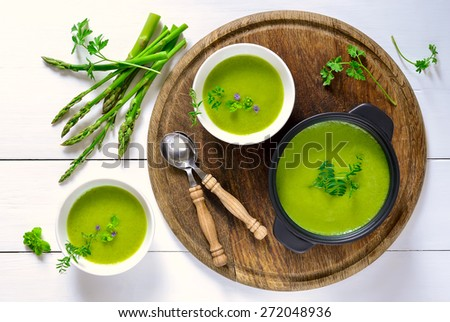 Green spring pureed asparagus soup served in plates decorated with various garden herbs Stock photo ©