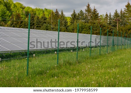 Green steel wire mesh fence with solar photovoltaic panels behind it. Photo stock ©