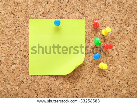 green sticky note over brown cork background