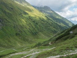 Green summer alpine mountain valley with winding river spring stream and Tyrolean walker at Stubai hiking trail, Stubai Hohenweg at Tirol, Austrian Alps