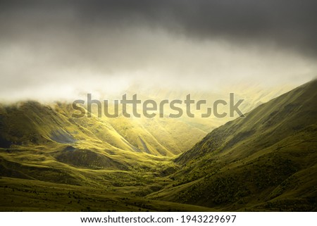 Green summer mountains in misty morning. Clouds over the mountain peaks. Gil-Su valley in North Caucasus, Russia.