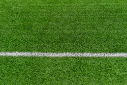 Green synthetic grass sports field with white line shot from above. Soccer, rugby, football, baseball sport concept
