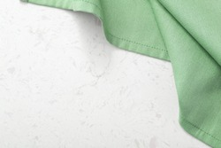Green tablecloth with on marble table background, top view