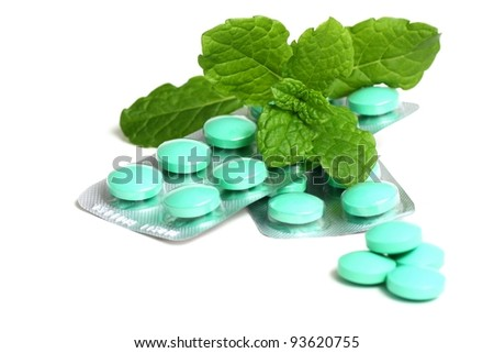 Green tablets in packaging covered with green herbal leaves close up isolated on white background