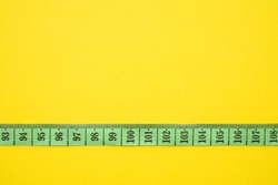 Green tape measure focus on one hundred centimeter on yellow background with copy space. Abstract business financial strategy, management, budget control, business plan concept.