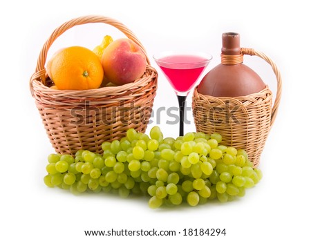 green tasty grapes and bottles in yellow baskets on white background