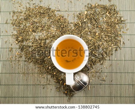 Green tea heart shape over bamboo mat top view with teacup