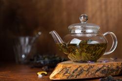 green tea in a glass teapot on dark background