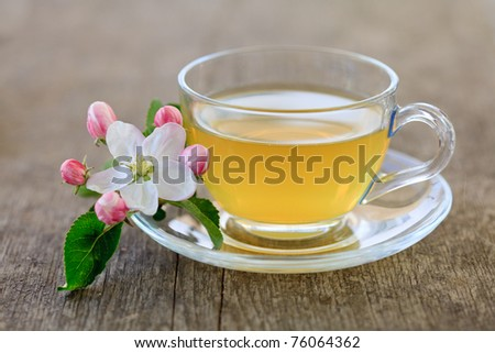 Green tea in glass cup and flowers on wooden table