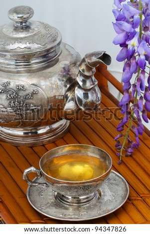 Green tea in the cup, the blue flowers of acacia on a bamboo tray