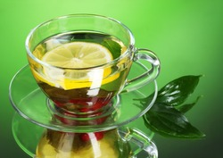 green tea in transparent cup with lime and berry on green background