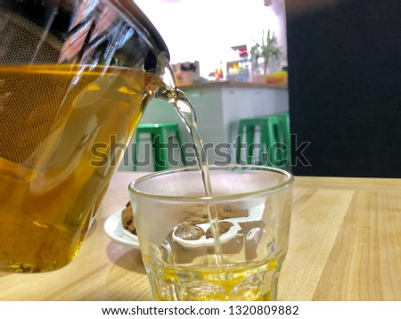 green tea is poured from a clear teapot into a clear glass