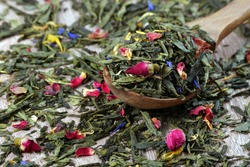 green tea leaves and dried rose flowers in a wooden spoon