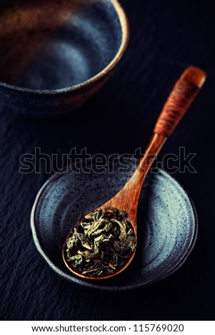Green tea leaves on a wooden spoon