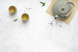 Green Tea Set -  iron teapot and ceramic teacups with green tea and leaves. Traditional asian tea composition on white background, copy space, top view.